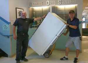 Jeff Williams and Ben Kim deliver a refrigerator donated by Iona Park for a PEACE Academy classroom.